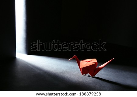 Origami crane on dark background with light - stock photo