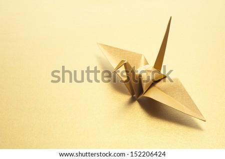 origami crane on gold background - stock photo