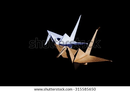 Origami cranes made from white and brown recycle paper isolated on black background - stock photo