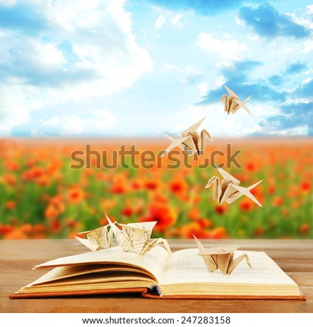 Origami cranes on book on nature background - stock photo