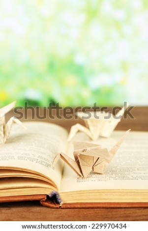 Origami cranes on old book on wooden table, outdoors - stock photo