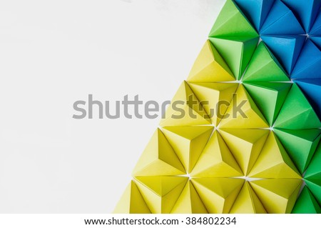 Origami 3 dimension shapes in green, blue and yellow colors with free copy space on the left side. Great for using in web. - stock photo