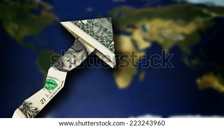 Origami dollar arrow pointing up over a world map  - stock photo