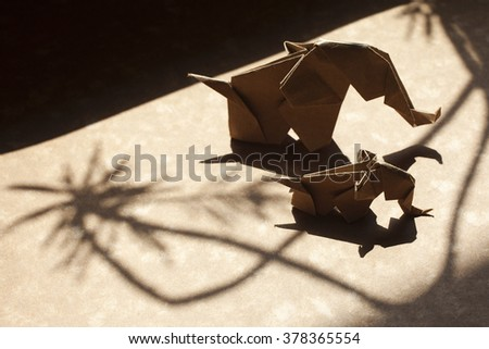 Origami elephant family made of craft paper on a beautiful shadow scene.