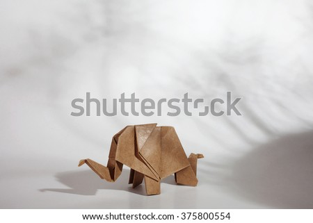 Origami elephant made of craft recycle paper on shadow scene. - stock photo