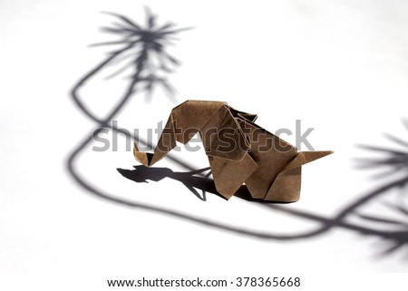 Origami elephant made of craft recycle paper on shadow scene over white background - stock photo