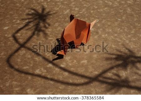 Origami elephant made of orange paper on a beautiful shadow scene. - stock photo