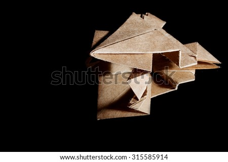 Origami frog made from brown paper on black background with reflection. - stock photo