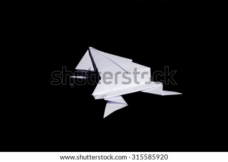 Origami frog made from white paper isolated on black background - stock photo