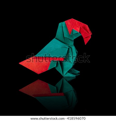 Origami macaw parrot sitting on a black background - stock photo