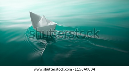 origami paper boat sailing on water causing waves and ripples - stock photo