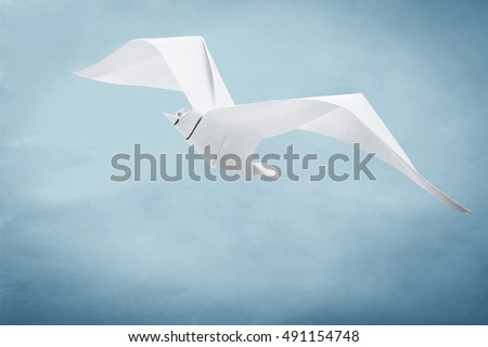 Origami paper seagull on a blue background