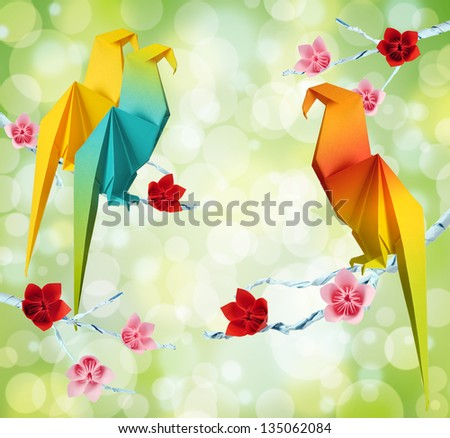 Origami parrots on a branches trees with flowers on green background - stock photo