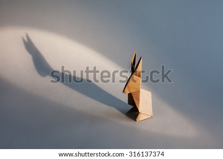 Origami rabbit on white background with light and shadow. - stock photo
