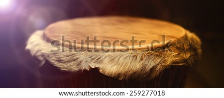 Original african djembe drum with leather lamina with beautiful hair in beautiful effect violet yellow light with dark background - stock photo