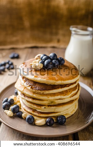Original american pancakes with berries, roasted nuts and milk behind, rustic style photo, place for advertisment - stock photo