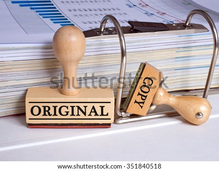 Original and Copy - two stamps with binder in the office - stock photo