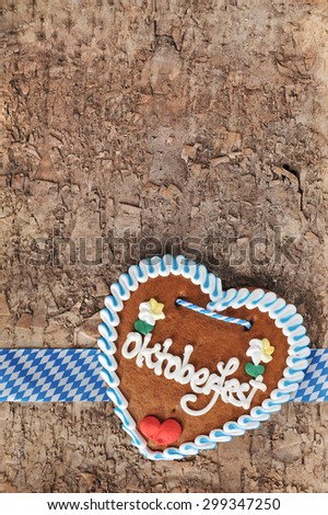 original bavarian Oktoberfest gingerbread heart from Germany on real brown tree bark - stock photo