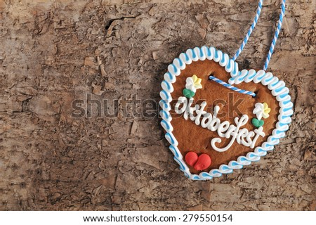 original bavarian Oktoberfest gingerbread heart on real brown tree bark - stock photo