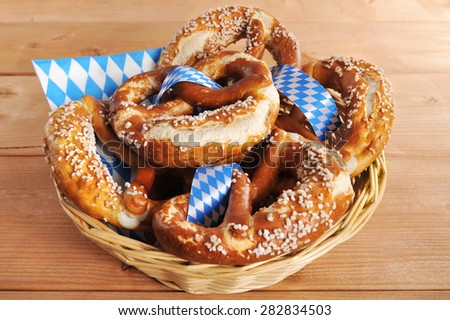 original bavarian Oktoberfest salted soft pretzels in a basket on wooden board