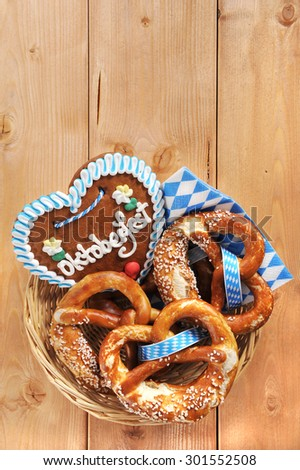 original bavarian Oktoberfest salted soft pretzels with gingerbread heart in a basket from Germany on wooden board - stock photo