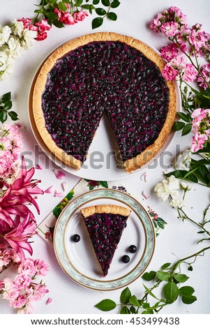 Original blueberry pie served on plate and decorated with pink flowers top view
