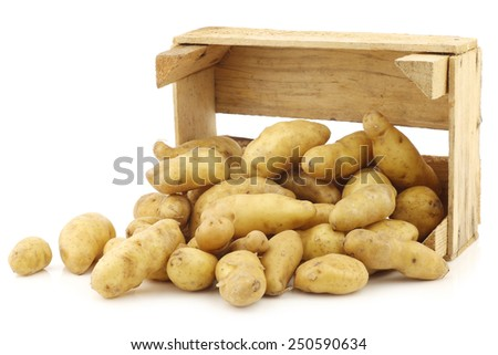"""original french """"ratte""""potatoes (Solanum tuberosum) in a wooden crate on a white background - stock photo"""