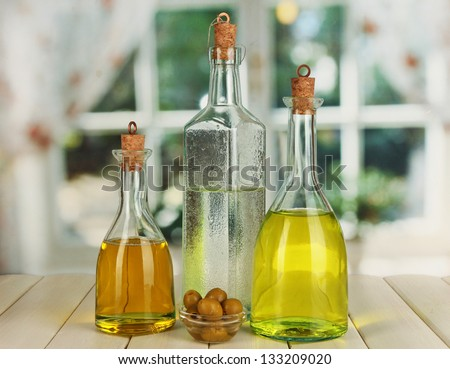 Original glass bottles with salad dressing on wooden table on window background - stock photo
