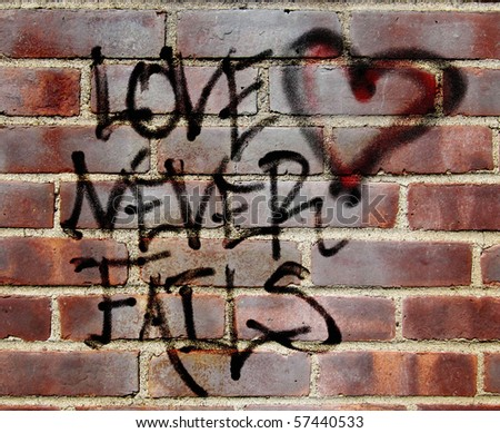 "original graffiti illustration of Corinthians 13 ""love never fails"" layered with a photograph of a brick wall - stock photo"