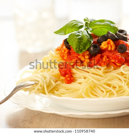 Original Italian spaghetti bolognese with basil and black olives with fork.