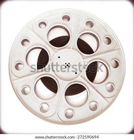 Original old big movie reel for 35 mm cinema  projector loaded with film in vintage color effect on neutral background - stock photo