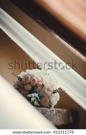 Original wedding bouquet made of flowers in pastel tones lies on a windowsill