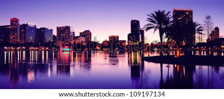 Orlando downtown skyline panorama silhouette over Lake Eola at dusk with urban skyscrapers. - stock photo