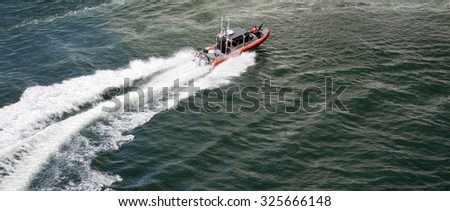 ORLANDO, FLORIDA - SEPTEMBER 26, 2015: A US Coast Guard 25 Foot Defender Class Boat Patrols the departure of a Cruise Ship into the open seas Orlando, Florida on September 26, 2015.
