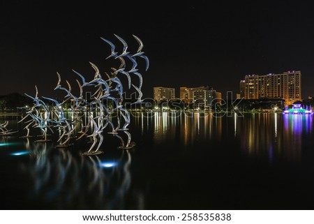 Orlando Lake Eola in the night and sculpture of colored birds - stock photo