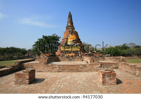 Ornament: ancient buddha statue in front of pagoda at Wat Worachet Tharam in Ayutthaya, Thailand