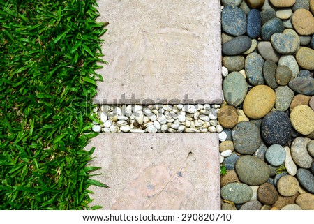 Ornament Stone footpath with pebble and grass in the garden - stock photo