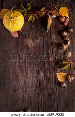 Ornament with pumpkin, acorns and autumn leaves on old wood as background - stock photo
