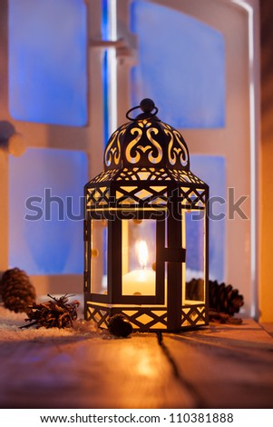 Ornamental Christmas lantern with a glowing candle illuminating a window in the evening light - stock photo