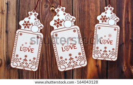 ornamental 3d rendered christmas labels with love sticker in front of a nice wooden background - stock photo