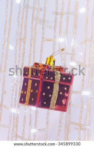 Ornamental red gift box on Christmas tree - stock photo