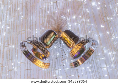 Ornamental silver bells hanging on Christmas tree - stock photo