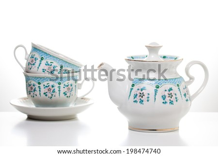 Ornamental tea set.  Two tea cups with saucers and teapot on white background.  Porcelain  dishes. Tea time. Decorative  background. Tableware - stock photo