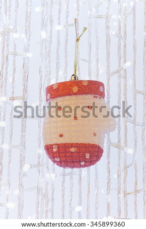 Ornamental velvet glove hanging on Christmas tree - stock photo