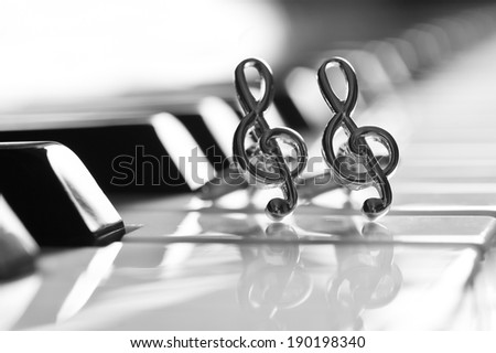 Ornaments in the form of a treble clef on piano keyboard - stock photo