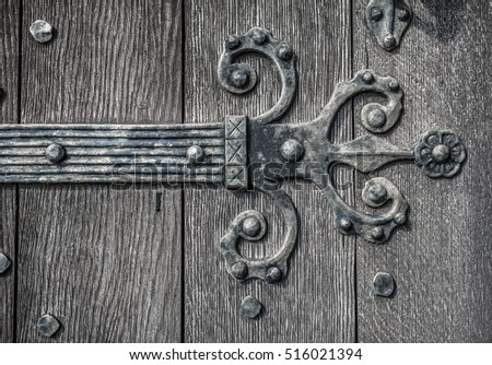 Ornate and weathered medieval church door hinge pattern.