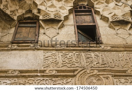 Ornate architecture in the ancient Wikala al-Qutn, the caravanseai (or inn) of cotton at the heart of Khan El Khalili bazaar in Cairo, Egypt. It dates from 1511. The windows were for merchants' rooms. - stock photo