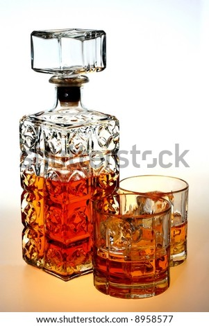 Ornate bottle and glasses of whiskey and ice against white background. - stock photo
