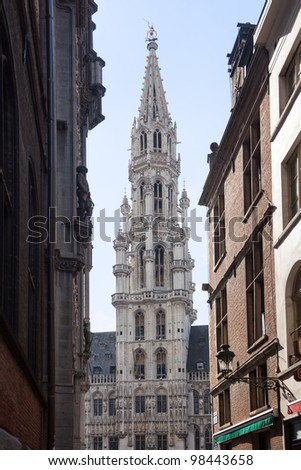 Ornate Brussels Town Hall in Grand Place through narrow alley - stock photo