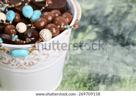 Ornate bucket filled with chocolates and beads - stock photo